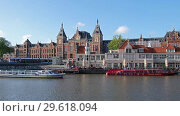 View on Amsterdam Centraal Station over chanal with passenger ships. (2018 год). Редакционное видео, видеограф Serg Zastavkin / Фотобанк Лори