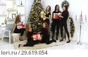 Six beautiful models taking a photo together in the studio Holding christmas gifts in the boxes. Smiling and having fun. Стоковое видео, видеограф Константин Шишкин / Фотобанк Лори