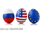 Купить «Three Easter eggs painted in the colors of flags of Russia, America and the European Union isolated on a white background. Concept on theme of friendship between countries», фото № 29619534, снято 15 декабря 2018 г. (c) Сергей Чайко / Фотобанк Лори
