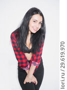 Купить «Cheerful young brunette posing in a plaid shirt.», фото № 29619970, снято 8 января 2016 г. (c) Сергей Сухоруков / Фотобанк Лори