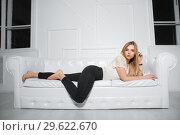 Купить «Sexy blonde posing on a white sofa in the studio», фото № 29622670, снято 22 февраля 2016 г. (c) Сергей Сухоруков / Фотобанк Лори