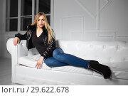 Купить «Thoughtful woman posing lying on a sofa in a studio», фото № 29622678, снято 22 февраля 2016 г. (c) Сергей Сухоруков / Фотобанк Лори
