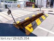 Купить «Road barrier with yellow and black striped caution pattern,», фото № 29625354, снято 23 июня 2018 г. (c) FotograFF / Фотобанк Лори