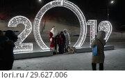 Купить «Люди фотографируются с Дедом Морозом и Снегурочкой возле огромных цифр 2019», видеоролик № 29627006, снято 31 декабря 2018 г. (c) А. А. Пирагис / Фотобанк Лори