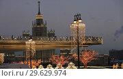 Купить «Фонари на набережной и светящийся мост в парке Зарядье с видом на высотку. Вечерняя Москва», видеоролик № 29629974, снято 29 декабря 2018 г. (c) Яна Королёва / Фотобанк Лори