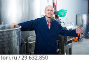 Купить «positive mature man working in wine secondary fermentation section», фото № 29632850, снято 16 января 2019 г. (c) Яков Филимонов / Фотобанк Лори