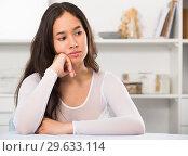 Купить «Gloomy girl sitting at the table», фото № 29633114, снято 30 мая 2017 г. (c) Яков Филимонов / Фотобанк Лори