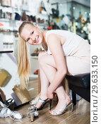 Купить «Smiling female is trying on brilliant heeled sandals», фото № 29633150, снято 27 мая 2017 г. (c) Яков Филимонов / Фотобанк Лори