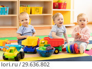 Купить «Group of babies is playing on floor in nursery. Children in the day care center. Fun in the children's playroom», фото № 29636802, снято 18 мая 2019 г. (c) Оксана Кузьмина / Фотобанк Лори