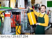 Купить «Seller displaying various items in garden equipment shop», фото № 29637294, снято 2 марта 2017 г. (c) Яков Филимонов / Фотобанк Лори