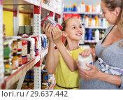 Купить «Woman with daughter are choosing fresh goods in food department», фото № 29637442, снято 5 июня 2017 г. (c) Яков Филимонов / Фотобанк Лори