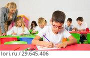 Купить «Diligent schoolboy drawing at lesson», фото № 29645406, снято 15 ноября 2018 г. (c) Яков Филимонов / Фотобанк Лори