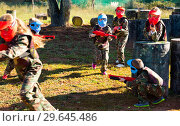 Купить «Children paintball players of opposite teams playing in shootout outdoors», фото № 29645486, снято 24 ноября 2018 г. (c) Яков Филимонов / Фотобанк Лори