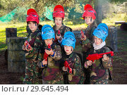 Купить «Friendly group of children paintball players in camouflage posing with guns on paintball playing field outdoors», фото № 29645494, снято 24 ноября 2018 г. (c) Яков Филимонов / Фотобанк Лори