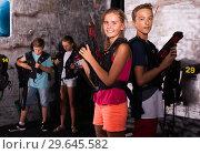 Купить «Girl and boy standing back to back with laser guns», фото № 29645582, снято 4 августа 2020 г. (c) Яков Филимонов / Фотобанк Лори
