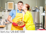 Купить «a man in an apron with a pie and her beloved wife, a portrait in the kitchen», фото № 29647550, снято 14 октября 2018 г. (c) Константин Лабунский / Фотобанк Лори