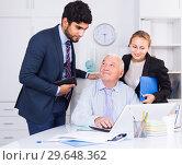 Купить «Employees are demonstrating reports on laptop to mature boss», фото № 29648362, снято 27 июня 2017 г. (c) Яков Филимонов / Фотобанк Лори