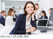 Happy young businesswoman foreground in busy open plan office. Стоковое фото, фотограф Яков Филимонов / Фотобанк Лори