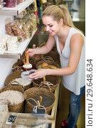 Купить «Young female picking with scoop beans», фото № 29648634, снято 21 января 2019 г. (c) Яков Филимонов / Фотобанк Лори