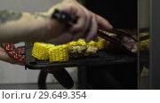 Купить «Side View Of The Hands Of The Cook Take Out A Baking Sheet», видеоролик № 29649354, снято 4 апреля 2020 г. (c) Pavel Biryukov / Фотобанк Лори