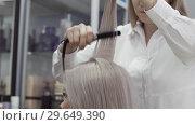 Купить «Woman Hairdresser Doing Hairstyle With The Help Of An Ironing», видеоролик № 29649390, снято 26 мая 2020 г. (c) Pavel Biryukov / Фотобанк Лори