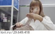 Купить «Cute Young Woman Hairdresser Doing Hairstyle With Ironing To Client Girl», видеоролик № 29649418, снято 26 мая 2020 г. (c) Pavel Biryukov / Фотобанк Лори