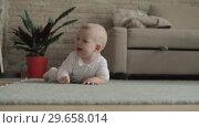Купить «Lovely eight months baby girl on the floor at home», видеоролик № 29658014, снято 24 июня 2019 г. (c) Данил Руденко / Фотобанк Лори