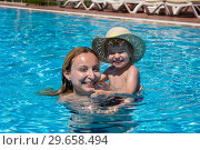 Купить «Mom and little daughter bathe in the outdoor pool on vacation», фото № 29658494, снято 18 июля 2019 г. (c) Светлана Кузнецова / Фотобанк Лори