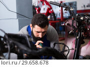 Купить «Worker repairing motorbike», фото № 29658678, снято 20 июня 2019 г. (c) Яков Филимонов / Фотобанк Лори