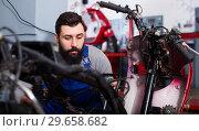 Купить «Worker repairing motorbike», фото № 29658682, снято 19 января 2019 г. (c) Яков Филимонов / Фотобанк Лори