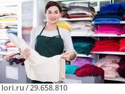 Купить «Seller showing white fabric», фото № 29658810, снято 4 января 2017 г. (c) Яков Филимонов / Фотобанк Лори