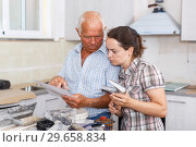 Купить «Confused woman with elderly father reading work manual on mixer tap», фото № 29658834, снято 19 июня 2018 г. (c) Яков Филимонов / Фотобанк Лори