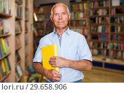 Купить «Portrait of positive intelligent older man in library with book in hands», фото № 29658906, снято 11 июня 2018 г. (c) Яков Филимонов / Фотобанк Лори