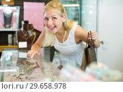 Купить «Smiling female customer looking jewellery gifts», фото № 29658978, снято 16 июля 2019 г. (c) Яков Филимонов / Фотобанк Лори
