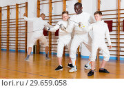 Купить «Focused boys fencers attentively listening to professional fencing coach in gym», фото № 29659058, снято 30 мая 2018 г. (c) Яков Филимонов / Фотобанк Лори
