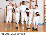 Купить «Group portrait of young fencers with coaches holding rapiers in training room», фото № 29659062, снято 30 мая 2018 г. (c) Яков Филимонов / Фотобанк Лори