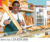 Купить «Positive baker presenting fresh baked products», фото № 29659066, снято 12 ноября 2018 г. (c) Яков Филимонов / Фотобанк Лори