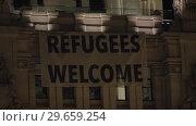 Купить «Night view of Refugee Welcome banner on Cybele Palace in Madrid», видеоролик № 29659254, снято 11 июля 2018 г. (c) Данил Руденко / Фотобанк Лори