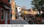 Купить «Brightly painted houses in the street with canal. Burano island, Italy», видеоролик № 29659490, снято 17 октября 2019 г. (c) Данил Руденко / Фотобанк Лори
