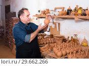 Купить «Elderly master at the pottery workshop», фото № 29662266, снято 12 октября 2016 г. (c) Яков Филимонов / Фотобанк Лори