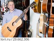 Купить «Man choosing new acoustic guitar in music store», фото № 29662306, снято 18 сентября 2017 г. (c) Яков Филимонов / Фотобанк Лори