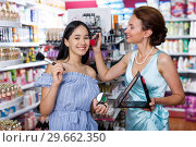 Купить «Girl and mother trying face powder and mirror at cosmetics shop», фото № 29662350, снято 21 июня 2018 г. (c) Яков Филимонов / Фотобанк Лори