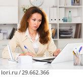 Купить «Female is working with documents and laptop», фото № 29662366, снято 30 мая 2018 г. (c) Яков Филимонов / Фотобанк Лори