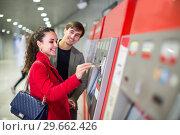 Купить «couple purchasing tickets», фото № 29662426, снято 22 октября 2019 г. (c) Яков Филимонов / Фотобанк Лори