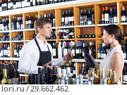 Купить «Seller helping woman customer with bottle of wine», фото № 29662462, снято 16 января 2019 г. (c) Яков Филимонов / Фотобанк Лори