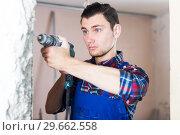 Купить «Builder handyman working with electric drill», фото № 29662558, снято 21 мая 2017 г. (c) Яков Филимонов / Фотобанк Лори