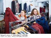 Купить «Women choosing new overcoat», фото № 29662658, снято 6 декабря 2018 г. (c) Яков Филимонов / Фотобанк Лори