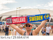 Купить «Russia, Samara, July 2018: football fan shows the flag of the football game England Sweden against the background of the stadium at the World Championships.», фото № 29664614, снято 7 июля 2018 г. (c) Акиньшин Владимир / Фотобанк Лори