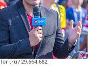Russia, Samara, July 2018: a microphone in the hands of a journalist leading a report from the World Cup. Редакционное фото, фотограф Акиньшин Владимир / Фотобанк Лори