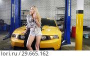 Купить «Car repair service. Young sexy woman in small shorts sitting on the hood of yellow sport car and smoking a cigarette», видеоролик № 29665162, снято 17 января 2019 г. (c) Константин Шишкин / Фотобанк Лори